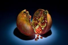 Fantastic pomegranate. Two parts of a pomegranate on a dark background. Beautiful art illumination Royalty Free Stock Images
