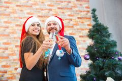 Beautiful couple on a Christmas party with champagne on a blurred background. Romantic christmas concept. Fantastic positive romantic couple in cute Santa hats Royalty Free Stock Photo