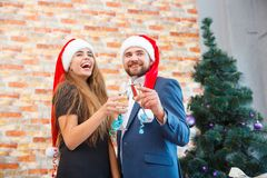 Beautiful couple on a Christmas party with champagne on a blurred background. Romantic christmas concept. Fantastic positive romantic couple in cute Santa hats Royalty Free Stock Image