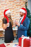 Beautiful couple on a Christmas party with champagne on a blurred background. Romantic christmas concept. Fantastic positive romantic couple in cute Santa hats Royalty Free Stock Photos