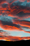 Fantastic red clouds in blue sky during sunset. Mountain silhouette Royalty Free Stock Images