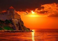 Fantastic red sunset. Medieval fortress on a background of red sunset. Digital artwork Stock Photography