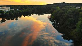 Colorful landscape of river near a forest under a beautiful sky with bright clouds during sunset Royalty Free Stock Image