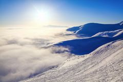 Fantastic scenery with the high mountains in snow, dense textured fog  in the cold winter day. Winter landscape with fog. Stock Photos