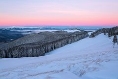Fantastic scenery with the high mountains in snow, dense textured fog and a sunrise in the cold winter day. Stock Photography