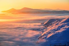 Fantastic scenery with the high mountains in snow, dense textured fog and a sunrise in the cold winter day. Royalty Free Stock Image