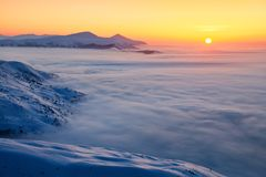 Fantastic scenery with the high mountains in snow, dense textured fog and a sunrise in the cold winter day. Mountains in fog. Stock Images