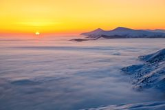 Fantastic scenery with the high mountains in snow, dense textured fog and a sunrise in the cold winter day. Royalty Free Stock Photography