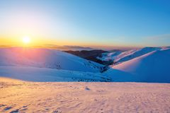Fantastic scenery with the high mountains in snow and a sunrise in the cold winter day. Stock Photo
