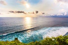 Fantastic scenic landscape sunset from Pura Uluwatu cliff, Bali,. Bright light rays of the sun illuminate the coast of the azure sea with foamy waves Stock Images