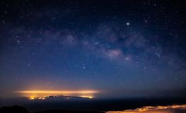 Fantastic shot of the Milky Way over a lit island royalty free stock photos