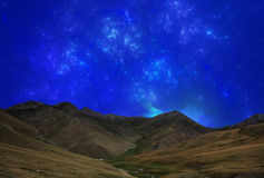 Fantastic star sky at night in mountain valley Stock Images
