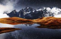 Fantastic starry sky on mountain lake Koruldi. Picturesque night Upper Svaneti, Georgia Europe. Caucasus mountains.  stock photos
