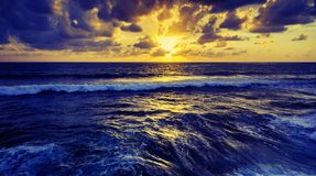 Fantastic stunning colorful sunset by the sea, waves and sunlight royalty free stock photos