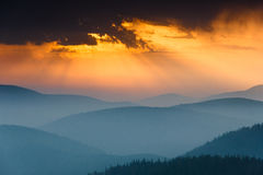 Fantastic sunrise above peaks of smoky mountain with the view into misty hills. Royalty Free Stock Images