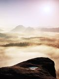 Fantastic sunrise on the top of the rocky mountain with the view into misty valley Royalty Free Stock Photo