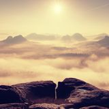 Fantastic sunrise on the top of the rocky mountain with the view into misty valley Stock Photos