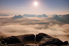 Fantastic sunrise on the top of the rocky mountain with the view into misty valley Stock Photo