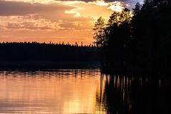 Fantastic sunset on the lake, dark pine forest reflecting in the calm water royalty free stock images