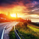 Fantastic sunset that leads into the mountains. Asphalt road wit Stock Image