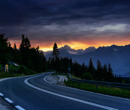 Fantastic sunset that leads into the mountains. Asphalt road wit Stock Images
