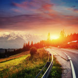 Fantastic sunset that leads into the mountains. Asphalt road wit Royalty Free Stock Photos