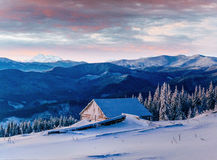 Fantastic sunset over snow-capped mountains and wooden chalets Stock Photo