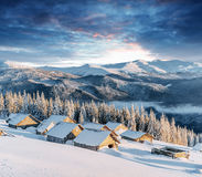 Fantastic sunset over snow-capped mountains and wooden chalets Stock Photos