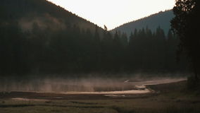 Fantastic view of the foggy hill and cloudy sky which glowing by sunlight. Dramatic scene of picturesque mountain lake stock video footage