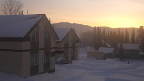 Fantastic winter landscape. Snowy mountains. Village in the mountains at amazing sunrise. Fantastic winter landscape. Snowy mountains. Village in the mountains Royalty Free Stock Images