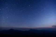 Fantastic winter meteor shower and the snow-capped mountains. Stock Photos