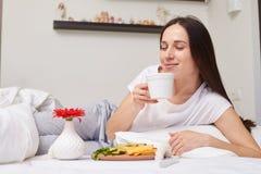 Fantastic woman smells dreamlike tea lying in bed Royalty Free Stock Image