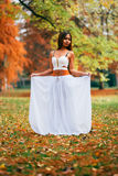 Fantastic young woman. beautiful fantasy girl fairy with white long dress in windy autumn park Royalty Free Stock Photos