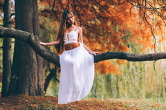 Fantastic young woman. beautiful fantasy girl fairy with white long dress in windy autumn park.  Royalty Free Stock Image
