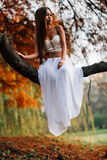 Fantastic young woman. beautiful fantasy girl fairy with white long dress in windy autumn park.  Stock Photography