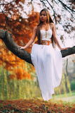 Fantastic young woman. beautiful fantasy girl fairy with white long dress in windy autumn park.  Royalty Free Stock Photo