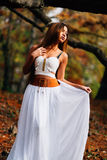 Fantastic young woman. beautiful fantasy girl fairy with white long dress in windy autumn park Royalty Free Stock Image
