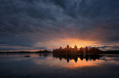Fantastically beautiful summer sunrise over Trakai Castle in Lithuania, with lonely fisherman in the boat and the sun`s rays. Royalty Free Stock Photography