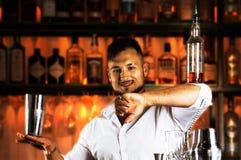 Fantastically knappe kerel houdt een fles op zijn elleboog en toont Stock Fotografie