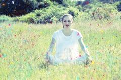 Fantasticare la giovane donna di yoga che si siede sull'erba con i punti variopinti Fotografia Stock