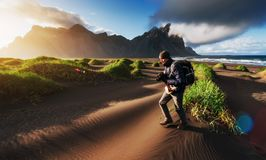 Fantastico ad ovest delle montagne e delle dune di sabbia vulcaniche della lava alla spiaggia Stokksness Turisti che attraversano fotografia stock libera da diritti