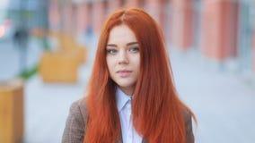 Fantastisch aantrekkelijk jong roodharig meisje in bruin bedrijfsjasje, op stedelijke straat, die in de camera Steadicam kijken stock footage