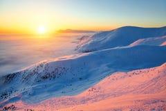 Fantastisch landschap met het hooggebergte in sneeuw, dichte geweven mist en een zonsopgang in de koude de winterdag Stock Foto's