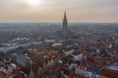 Fantastische de stadshorizon van Brugge met rode betegelde daken en Kerk van Onze Dametoren in de winterdag Weergeven aan middele royalty-vrije stock afbeeldingen