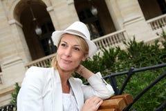 Fantastische Frau von mittlerem Alter mit dem Hut, der auf Bank sitzt Lizenzfreies Stockbild