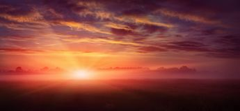 Fantastische Landschaft majestätischer nebelhafter Morgen über Wiese bunter Himmel mit bewölkten Wolken, Stockbild