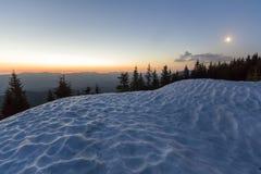Fantastische mening van avond in de winterbergen Donkergroene bovenkanten van pijnboombomen achter sneeuwheuvel en eerste heldere royalty-vrije stock afbeelding