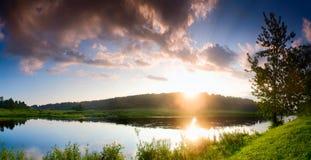Fantastische mistige rivier met vers groen gras in het zonlicht Royalty-vrije Stock Afbeeldingen