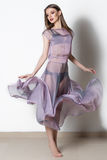 Fantastische Modefrau in einem flüssigen transparenten Kleid mit hellem Make-up im Studio stockbild