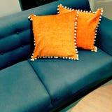 Fantastische orange Kissen, die ein Sofa verzieren Lizenzfreies Stockfoto